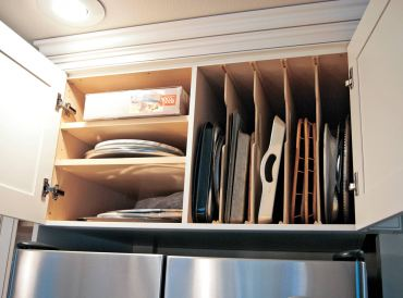 Platters and cookie sheets — neatly utilizing the space above the refrigerator.