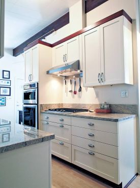 Mixed drawer front styles with cottage style cabinetry in a painted finish with cherry moldings. (Photo courtesy A Kitchen That Works)