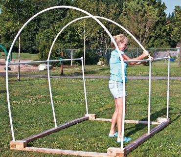 "Step 7a. Three 8-foot sections of PVC bend to put the ""hoop"" in hoop house."