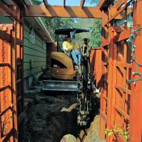 Trenching the new septic lines through the narrow side yard without damaging the house, fence, arbor and gate required an expert equipment operator; equipment had to be brought through a neighboring property. (Photo courtesy Jean Clark)