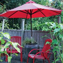 A weighty ceramic pot is cleverly used to hold the umbrella that shades vintage metal chairs in the upper garden. (Photo courtesy Colleen Miko)