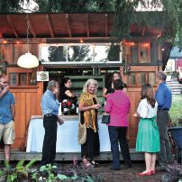 The shed serves as a convenient location for the bar during the Harvest dinner. Darin Clark, Doug Millard, Brandy Trunnel, Kerri Bozeman, Renae Hammel, Venita Goodrich, Tiffany Royal and Kevin Koski mix and mingle. (Photo courtesy Kathryn Photography)