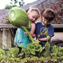 A favorite task for Sydney and Samson: watering lettuce plants. (Photo courtesy Bethany Raelene Studio)