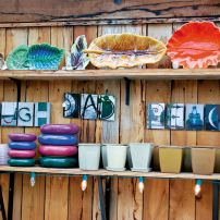Just part of the colorful (and display only) collection of Cheryl Pelkey's vintage leaf platters with pottery and decor to liven up your home or patio on shelves.