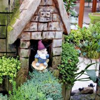 A smiling gnome peeks out from a carved wood castle planted with creeping plants.