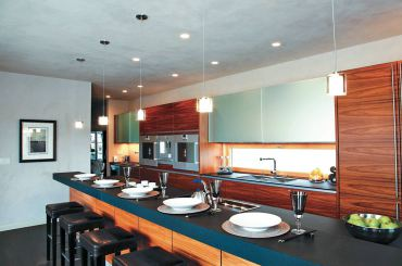 The kitchen in this photograph combines recessed can lights, pendant lights and under-cabinet lighting, providing layers of lighting that can be added or subtracted at a flip of a switch. (Photo courtesy Stone Lighting Design)