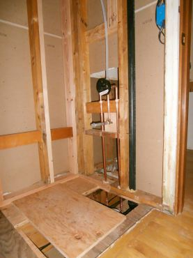 Repaired wall and floor in tub/shower area waiting for plumber to set drain