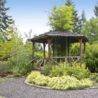 The gazebo anchors display beds and houses a black bamboo in its center.
