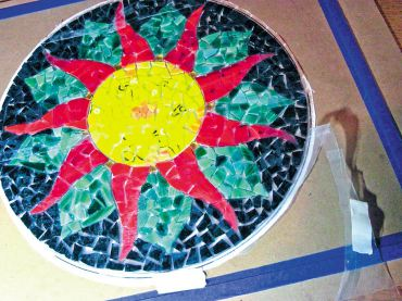 Once the glass design is laid out, cover the top with a clear adhesive film such as tile tape or mosaic mount so that it doesn't shift as you turn the whole thing upside down to apply adhesive.