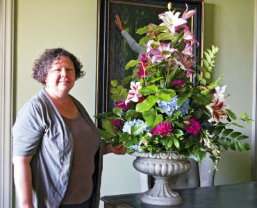 Tyler with a summer arrangement in the library featuring salal, zinnia, dahlia, Penstemon, Mahonia, oriental lilies and Hydrangea.
