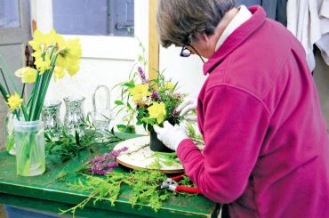 Volunteer Chrilo von Gontard uses a lazy susan to create balanced bouquets with bright daffodils and heath.