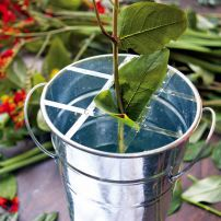 Transparent tape is used to make a supportive but inconspicuous grid to support flower stems and keep them in place.