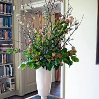 A tall, stately arrangement on the writing desk of Prentice Bloedel features Corylopsis, huckleberry, cherry, maple and Viburnum tinus.