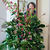 Tyler is reflected in the mirror in the hallway of the visitor's center and in the late winter floral design she created with cedar, Viburnum, Camellia, Sarcococca, cherry and flowering currant.