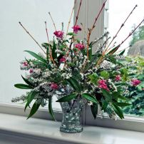 A late winter combination of white heath flowers, red flowering currant, Sarcococca and yellow-twig dogwood combine well in a small glass vase.