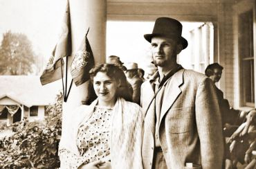 "Lorene and Henry stand on the front porch of the Puget Hotel for the centennial celebration in Port Gamble. Henry was known to many in town as ""Hank"" but not to Lorene. Lorene, who taught herself how to knit, only used ""hank"" when she referred to yarn. ""It's a hank of yarn or a skein of yarn, not my husband,"" she says."