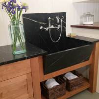 Quarried stone laundry sink with wall mounted faucet — Design by Vawn Greany, CKD, CBD, CAPS, NWSID of Collaborative Interiors