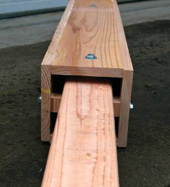 View into the bat's entrance at the base of the rocket box. Bolts anchor the box to the inner post and wood spacers maintain the proper 3/4-inch distance between the box and post. Notice that the 4-by-4 that the box itself is mounted on is untreated lumber to protect bats from toxins.