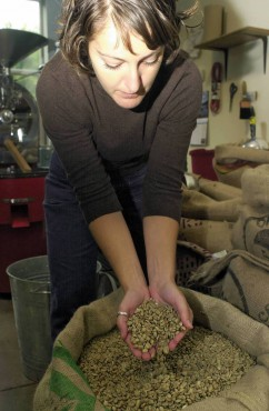 Grounds for Change co-founder, Stacy Marshall, holds some raw beans in her hand.