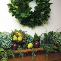A wreath of salal brings a fresh evergreen touch to a mantle decorated with fruit, rosemary and cedar.