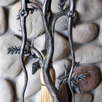 Elijah makes a good number of fireplace sets and bar-b-que tools that can be customized to different artistic styles and themes, including this one with intricate pine-cone detailing.