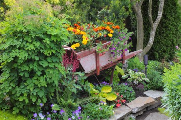 A wooden wheelbarrow — planted with colorful annuals and tender plants — came to live in their garden after Rudell and her brother saw a wooden one during a garden tour. Her brother found one for her online at craigslist.