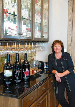 "Moore with three of her ""Make the DASH Count"" label wines; at far right is The Innkeeper Cabernet Sauvignon, named to honor her mother."