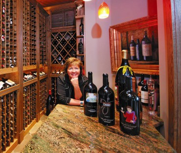 Moore, in one of her two wine cellars, displays four of her nearly 100 custom-etched and hand-painted wine bottles from Fresh Northwest Design in Gig Harbor.