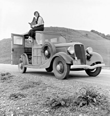 Photograph of Dorothea Lange, photographer for the Farm Security Administration (FSA), sitting on top of a 1933 Ford Model B, holding her camera, February of 1936. (This image was taken by Paul S. Taylor)