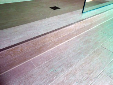 Wood grain plank porcelaine tiles are perfect for bathrooms — Design by Timeless Kitchen Designs