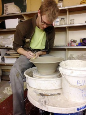 Jordan Meyer, whose work will be displayed at one of the tour studios, works at his potter's wheel.