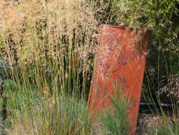 Metal sculpture enhances the sea of grass in front of it.
