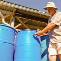 Eugene Brennan stands on the platform elevating his rain barrels, discussing how the height improves the function of gravity-fed drip lines and how the pump in the cistern fills the barrels.