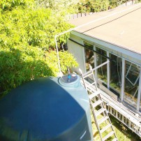 Brennan's 3,000-gallon cistern is filled by rain from the garage roof, minimally filtered and then pumped over the roof to the main garden. Filled with water, the tank weighs 12 tons.