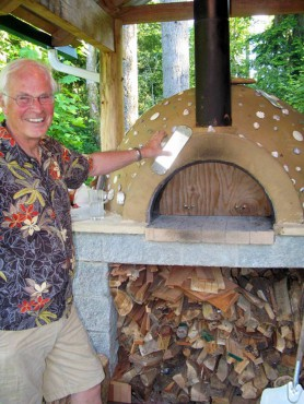 Don Heppenstall demonstrates the temperature differential between the outside of his oven at about 90 degrees and the inside, which can be as high as 700.