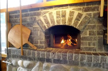 "A small warming fire can be seen through the oven door of the Fortners' oven. To the left is a ""peel,"" used to put loaves in and out of a hot oven."