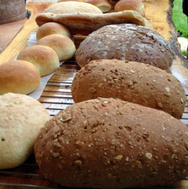 "Breads ready to be cut and served at a ""Loafers"" foodie event."