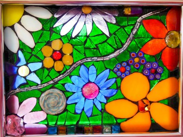 Exuberant window hanging designed with mirrored glass and ceramic flowers to reflect interior light and stained glass and millefiori beads to glow with backlight