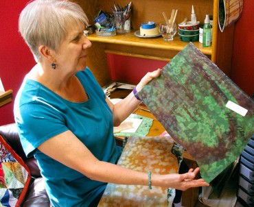 Louise Martin admires sheets of Uroboros handmade art glass given to her by stained-glass artist Haldean Windsor.