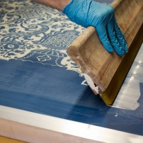 Paint is applied to a screen, revealing a lovely traditional patterned wallpaper.