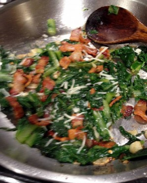 Skillet of ready to serve sautéed dandelion greens with bacon