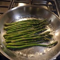 Asparagus simmering in shallow skillet
