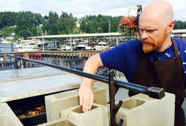 Chef Thad Lyman from Brix 25º builds up the coals on the outdoor grill for the pork belly course.