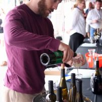 Representative from Rasa Winery pours a taste for a guest.