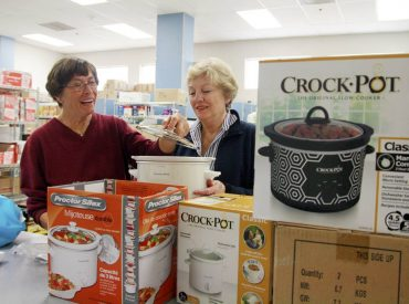 At Key Peninsula Middle School's assembly point, from left, Karen Jorgenson and Key Peninsula Lions Club member Cindy Robison are sorting crockpots for the Food Backpacks 4 Kids program. Jorgenson initiated the crockpots addition to the program in 2014, and the KP Lions contributed over 30 of them. (Photo courtesy Hugh McMillan)