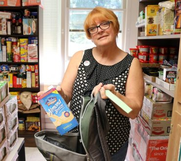 Myra Battin holds a carton of almond milk, donated for children who cannot tolerate cow's milk.
