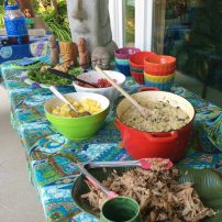 A tiki theme includes kálua pork and salads.