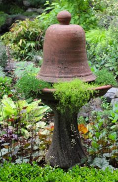 For height in a garden bed, a cloche sits on top of the birdbath and adds an appealing touch of whimsy.
