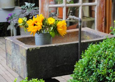 An old, heavy, cement trough from an antique shop is repurposed for a sink.