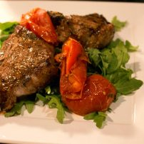 Broiled lamb chop, roasted herb romas, on a bed of arugula